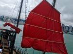 Fiery red sail on a junk boat docked next to the Tsim Sha Tsui Promenade