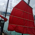 Fiery red sail on a junk boat docked next to the Tsim Sha Tsui Promenade